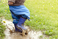Child in puddle boots jumping muddy after rain Royalty Free Stock Images