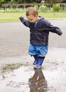 Child in puddle happy toddler playing after the rain Stock Photos