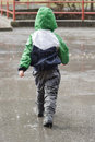 Child in rain walking on street heavy back view Royalty Free Stock Photo