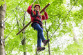 Child reaching platform climbing in high rope course Royalty Free Stock Photo