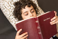 Child reading the bible young hispanic and studying holy at home daily devotional and reverence of a boy taking a break and Royalty Free Stock Image