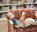 Child reading a book on a couch at the library Royalty Free Stock Photo