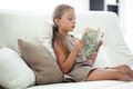Child reading book portrait of years old on the sofa at home Stock Image