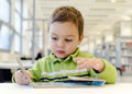 Child reading book toddler children picture on low table in public library Stock Image