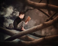 Child reading old story book on tree branch a little boy is sitting a with an owl in the dark woods for an education or Stock Photo
