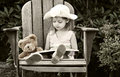 Child reading to her teddy bear Royalty Free Stock Photo