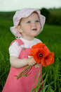 Child with red flower amongst green grass Royalty Free Stock Images