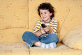 Child with the remote control of television Royalty Free Stock Photo