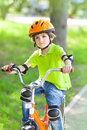 Child rides bike outdoors dressed in a colourful safety helmet and fleece green jacket Royalty Free Stock Image