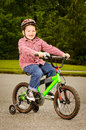 Child riding bike with safety helmet outdoors Royalty Free Stock Photography