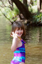 Child by the river little girl smiling and waving on a summer day Royalty Free Stock Images