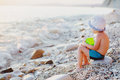 Child on a rock on the beach looking at oncoming waves at sunset Royalty Free Stock Photos