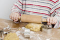 Child rolling dough on wooden desk image of hands and is making cookies with a pin Stock Images
