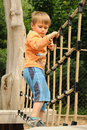 Child on rope barrier clever young in children park Royalty Free Stock Photo