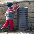 Child at rubbish bin small putting a waste or litter in a street can or Royalty Free Stock Photos