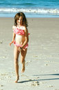 Child running on beach pretty little girl in swimsuit a Stock Photo