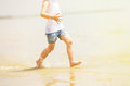 Child running beach shore splashing water tinted photo Royalty Free Stock Image