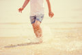 Child running beach shore splashing water tinted photo Stock Photos