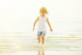 Child running beach shore splashing water tinted photo Stock Images