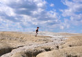 Child running between earth and sky young boy walking on a mud volcano filed with cloudy in background Stock Photos
