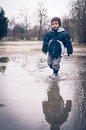 Child running in a pool of dirty water after raining spring bucharest romania Stock Images
