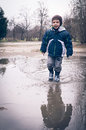 Child running in a pool of dirty water smiliing and smiling after raining spring bucharest romania Stock Photo