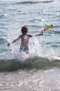 Child running in waves happy sea Stock Image