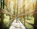 Child running in woods with sunlight a little is on a wooden trail the trees rays for a freedom or adventure concept Royalty Free Stock Images