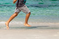 Child runs on the beach closeup legs only barefoot Royalty Free Stock Images