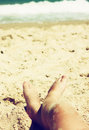 Child s feet in the sand filtered image Royalty Free Stock Photo
