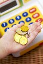 Child's Hand With Coins And Toy Cash Register Stock Image