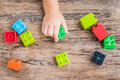 Child`s hand and colorful toy building cubes. Top view.