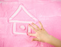 Child`s hand draws a beautiful house of your dreams.