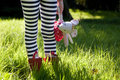 Child's Stripy Legs In A Meadow.