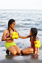 Child safety teen girl helping her younger sister to wear arm band of water Stock Photography