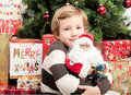 Child with santa doll in front of christmas tree Royalty Free Stock Photo