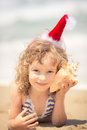Child in santa hat at the beach happy having fun tropical christmas holidays concept Stock Image
