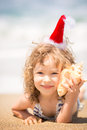 Child in santa hat at the beach happy having fun tropical christmas holidays concept Royalty Free Stock Photography