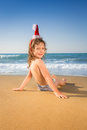 Child in santa hat at the beach happy having fun tropical christmas holidays concept Royalty Free Stock Image