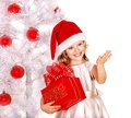 Child in santa hat with gift box near white christmas tree isolated Stock Photography
