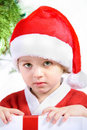 Child in a Santaclaus costume with a present. Stock Images
