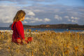 Child sat on coastline side view of field looking out to sea Royalty Free Stock Photo