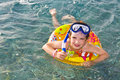 Child in scuba mask swimming on inflatable ring Royalty Free Stock Photo