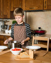 Child serving Borshch, traditional Russian and Ukrainian soup. Pouring soup into a plate with ladle from pan in kitchen. Royalty Free Stock Photo
