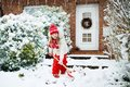 Child shoveling snow. Little girl with spade clearing driveway after winter snowstorm. Kids clear path to house door after Royalty Free Stock Photo