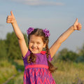 Child showing thumbs up outdoors small symbol Royalty Free Stock Image