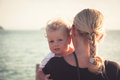 Child with a sincere look hugging his mother sitting on her hands and looking at camera Royalty Free Stock Photo