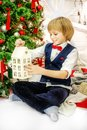 The child sits at the tree and looks at the Christmas house. Boy Royalty Free Stock Photo