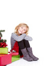 Child sitting next to a christmas tree with presents with an isolated white background Stock Photography