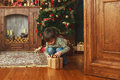 Child sitting under the Christmas tree with gifts Royalty Free Stock Photo